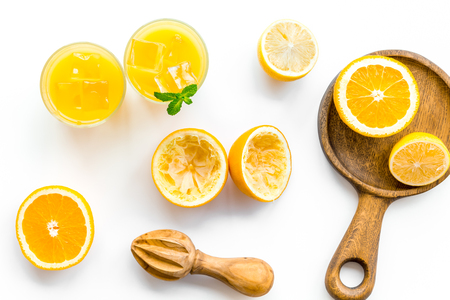 Squeeze fresh oranges with juicer. Orange juice in glass near half cut oranges on white background top view. Banco de Imagens