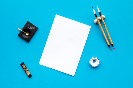 Lesson of calligraphy concept. White blank sheet for lettering near writing accessories on blue background top view mockup