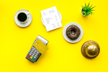 Payment terminal on restaurant desk near bill, service bell, coffee on yellow background top view