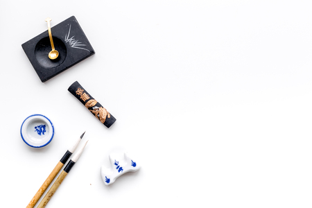 Accessories for Chinese or Japanese calligraphy. Special writing pen, ink on white background top view copy space