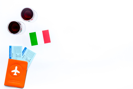Gastronomical tourism. Italian food symbols. Passport and tickets near Italian flag and glass of red wine on white background top view copy space