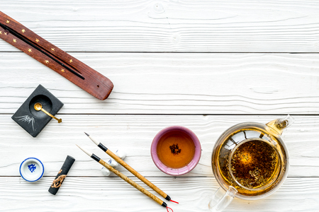 Chinese or Japanese traditions. Calligraphy and tea ceremony concept. Special writing pen, ink near teapot and cup of tea, incense on white wooden background top view space for text