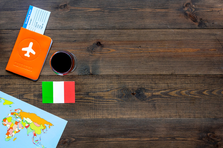 Gastronomical tourism. Italian food symbols. Passport and tickets near Italian flag, bottle of red wine, map of the world on dark wooden background top view space for text