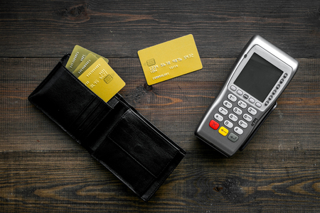 Pay by bank card, pay by credit card. Payment terminal near card and wallet with bank and credit cards on dark wooden background top view