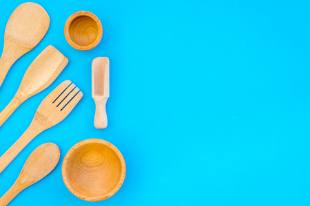 Woodenware set with spoon, fork and bowl on blue background top view space for text Stock Photo