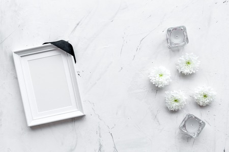 Photo frame, mockup with black ribbon near flowers, candles on white background top view. Stock Photo