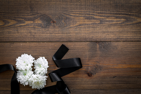 Funeral symbols. White flower near black ribbon on dark wooden background top view space for text Zdjęcie Seryjne