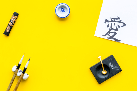 Chinese or Japanese calligraphy concept. Hieroglyph love near traditional written accessories on yellow background top view. 스톡 콘텐츠