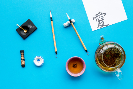 Lesson of calligraphy concept. Paper with hieroglyph love near writing accessories, teapot and cup of tea on blue background top view. 스톡 콘텐츠