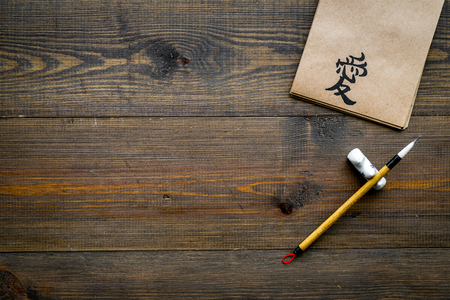Chinese traditional calligraphy concept. Asian hieroglyph love in craft paper notebook near special writing pen on dark wooden background top view copy space Stock fotó - 113102111