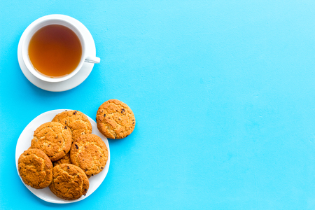 Dessert for evening tea. Cup of tea, fresh homemade cookies on blue background top view. Stock Photo