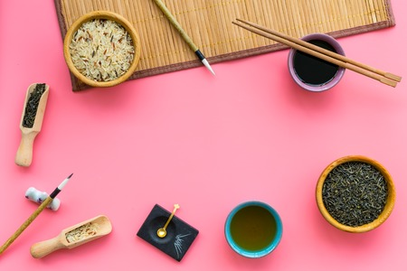 Chinese traditional symbols concept. Tea, rice, hieroglyph love, bamboo table mat, chopsticks, soy sauce on pink background top view frame.