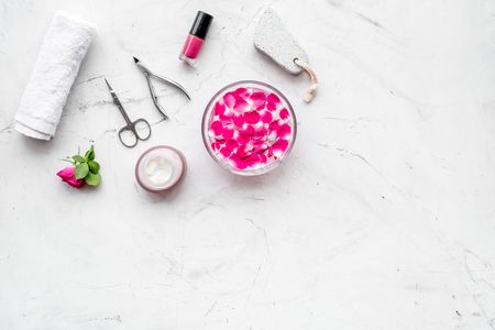 manicure equipment with nail polish and rose petals on white stone background top view mockup