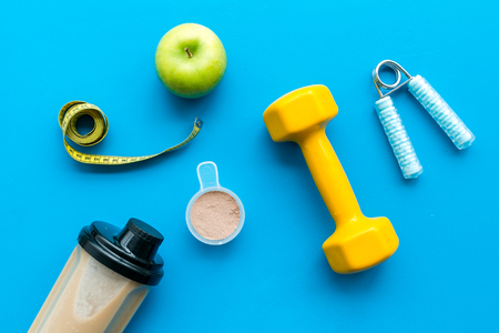 Sport nutrition set with protein powder for cocktail and scoop on blue desk background top view space for text Stock Photo