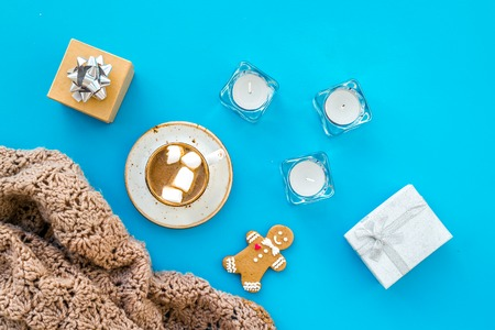 Romantic winter composition with hot drink. New Year or Christmas Eve. Cocoa with marshmallow, gift box, gingerbread man, wool blanket, fir branches on blue background top view.