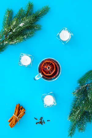 Winter beverage for New Year or Christmas Eve. Mulled wine near fir branches, candles, cinnamon on blue background top view.