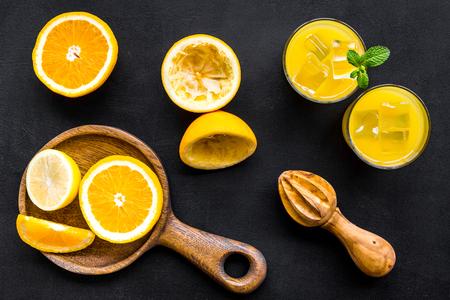 Squeeze fresh oranges with juicer. Orange juice in glass near half cut oranges on black background top view. Banco de Imagens