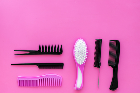 Female hairdresser desk with accessories and combs on pink background top view mock up. Stock Photo