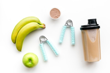 Nutrition for workout with protein cocktail and banana on white table background top view mockup