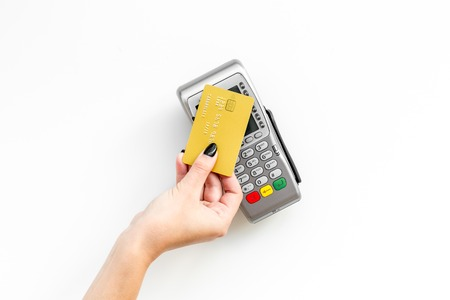 Pay by payment terminal. Paypass  technology. Woman's hand hold credit card, bring card to terminal  on white background top view. Фото со стока