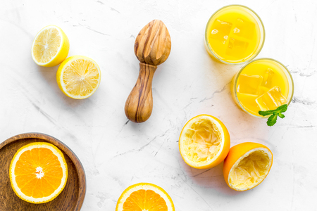 Squeeze fresh oranges with juicer. Orange juice in glass near half cut oranges on white stone background top view.
