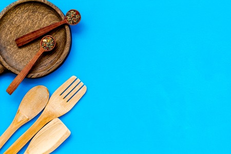 Fork, spoon, pan in woodenware set on blue table background top view space for text Stock Photo