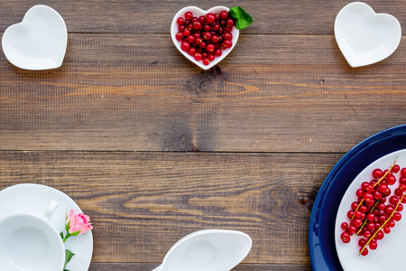 Simple color table setting for celebration with roses, white plates and wineberry on wooden table background top view mock up.