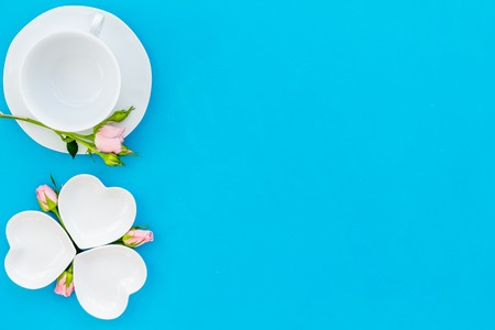 Simple color table setting for celebration with roses, white plates and heart-shaped saucers on blue kitchen table background top view mock up