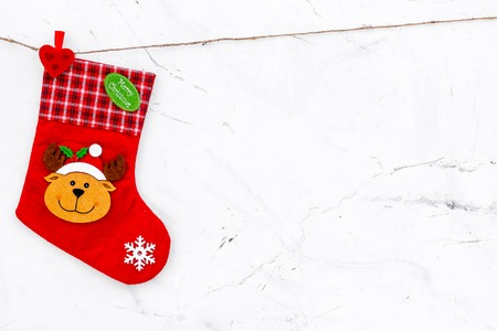 Decorative Christmas socks. Empty socks for gift hanging off a thread on white stone background top view.