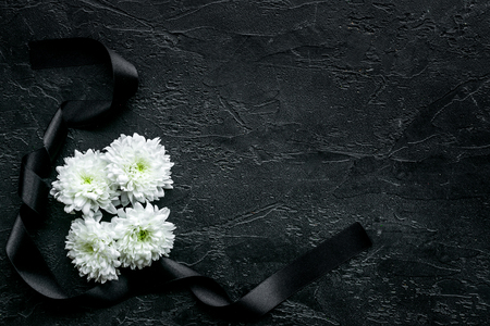 Funeral symbols. White flower near black ribbon on black background top view. Stockfoto