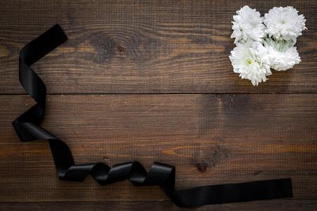 Funeral symbols. White flower near black ribbon on dark wooden background top view. Zdjęcie Seryjne - 113239310