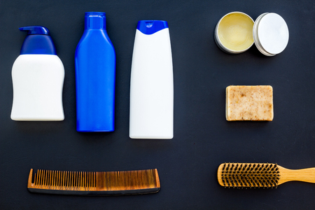 Barber workspace with equipment. Shampoo bottle and comb on dark table background top view space for text