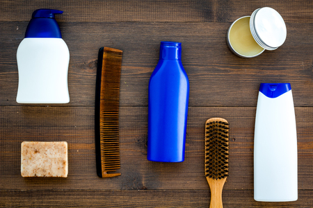 Shampoo bottle and comb for man care in barbershop on wooden background top view mockup