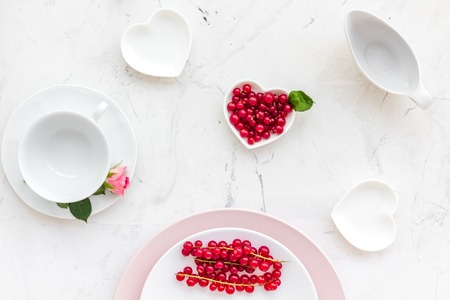 Simple color table setting for celebration with roses, pink plates and wineberry on white table background top view. Stock Photo