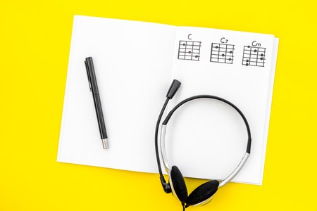 Desk of musician for songwriter work with headphones and notes on yellow background top view