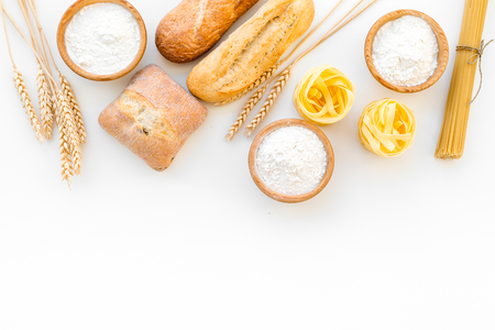 Farinaceous food. Fresh bread and raw pasta near flour in bowl and wheat ears on white background top view. Imagens
