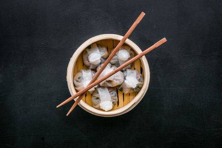 Chinese food set with dim sum, sticks on black desk background top view