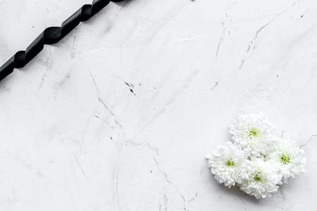 Begräbnissymbole. Weiße Blume nahe schwarzem Band auf Draufsicht des weißen Steinhintergrundes.