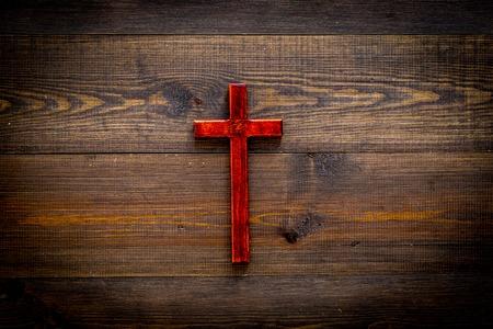 Funeral concept. Wooden cross on dark wooden background top view.