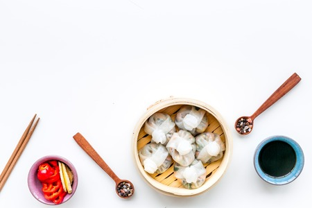 Dim sums with red pepper and vegetables with sticks and black tea in Chinese restaurant on white table background top view mockup