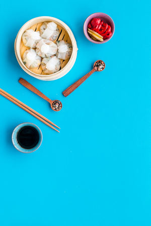 Chinese food set with dim sum, sticks and tea on blue desk background top view copy space