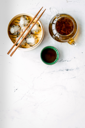 Chinese food set with dim sum, sticks and tea on marble desk background top view copy space
