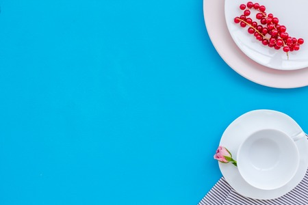 Simple color table setting for celebration with roses, wineberry, pink plates and heart-shaped saucers on blue table background top view mock up Stock Photo