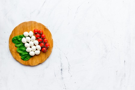Italian flag made of mozzarella cheese, cherry tomatoes, green basil on wooden cutting board on white stone background top view copy space Reklamní fotografie