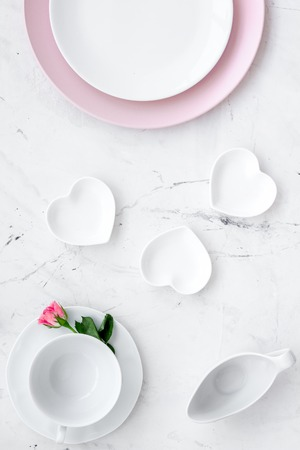 Simple color table setting for celebration with roses, pink plates and heart-shaped saucers on stone table background top view