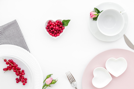 Simple color table setting for celebration with roses, wineberry, pink plates and heart-shaped saucers on white table background top view Stok Fotoğraf