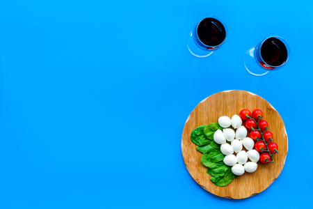 Italian cuisine, food concept. Italian flag made of mozzarella, tomatoes, basil on wooden cutting board near glass of red wine on blue background top view space for text