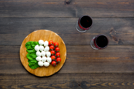 Italian cuisine, food concept. Italian flag made of mozzarella, tomatoes, basil on wooden cutting board near glass of red wine on dark wooden background top view copy space Reklamní fotografie - 113254551