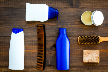 Barber workspace with equipment. Shampoo bottle and comb on wooden table background top view space for text