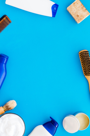 Instruments of male hairdresser with shampoo and comb in barbershop top view on light blue desk background mock up